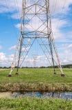 Hög spänningspylon i grönt landskap Arkivfoto