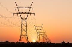 Hög spänningspylon under solnedgång Arkivfoto