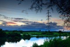 Hög spänningsstolpe för landskap på solnedgången Royaltyfri Bild
