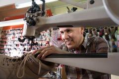 Hög specialist som syr skor på lädersymaskinen Arkivbild