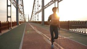 Hög spring för kvinnlig idrottsman nen på soluppgång på bron lager videofilmer