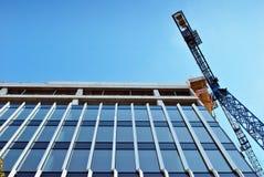hög stigning för byggnadskonstruktion under Platsen med kranar mot blå himmel royaltyfria foton