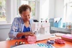 Hög svart kvinna som syr tyg genom att använda en symaskin Arkivbilder