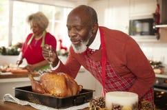 Hög svart man som tråcklar stekkalkon i förberedelsen för julmatställen, hans fru som hugger av grönsaker i bakgrunden, nära u royaltyfri bild