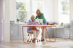 Hög symaskin för moder- och vuxen människadotterbruk hemma Royaltyfri Bild