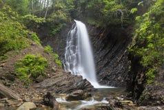Hög vattenfall i skogsedimentära stenarna, geologiska lager på bankerna royaltyfri bild
