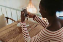 Hög vinkel av den afrikanska kvinnan som har att vila i kafé royaltyfri foto