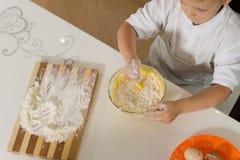 Hög vinkel av en liten pojke som bakar en kaka Royaltyfria Bilder
