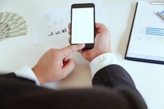 Hög-vinkel av mannen som i regeringsställning använder smartphonen med pengar på det arbetande skrivbordet arkivfoton