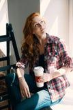 Hög vinkel på röd haired kvinna med koppen kaffe som är hemmastadd under renovering fotografering för bildbyråer