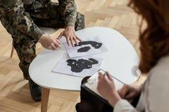 Hög vinkel på soldat i grön likformig med affischer under terapi med psykiatern royaltyfria bilder