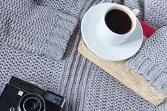 Hög-vinkel skott av en vit keramisk kopp med vitt kaffe, boken och en gammal kamera av en sweater fotografering för bildbyråer