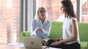 Hög yrkesmässig chefmentor som instruerar den unga kvinnliga allmäntjänstgörande läkaren med bärbara datorn