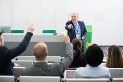 Höga affärsmanAsking Questions To kollegor, medan ge P Arkivbild