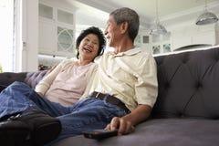 Höga asiatiska par hemma på Sofa Watching TV tillsammans Arkivfoton