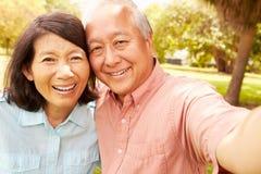 Höga asiatiska par som tar Selfie parkerar in, tillsammans Fotografering för Bildbyråer