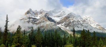 Höga berg av de kanadensiska steniga bergen som omges av moln längs den Icefields gångallén mellan Banff och jaspisen Arkivbilder