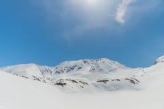 Höga berg under snö med klar blå himmel Arkivbild