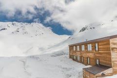 Höga berg under snö med klar blå himmel och kojan Royaltyfria Bilder