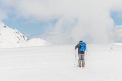 Höga berg under snö med klar blå himmel och kojan Arkivbild