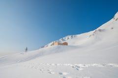 Höga berg under snö med klar blå himmel och kojan Royaltyfri Bild