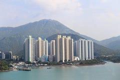Höga byggnader på fjärden och på bakgrunden av berg Stadslandskap på bakgrunden av naturen Arkivbild