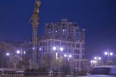 Höga byggnader under konstruktion med kranar på aftonen Lighteningmång--våning byggnader under konstruktion och kranar på nigh Fotografering för Bildbyråer