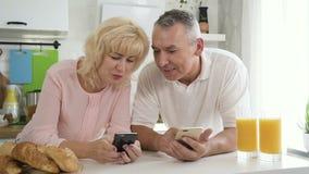 Höga familjpar som tycker om digital teknologi under frukosten i kök arkivfilmer