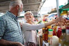 Höga familjpar som väljer den bio matfrukt och grönsaken på marknaden under veckoshopping royaltyfria bilder