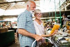 Höga familjpar som väljer den bio matfrukt och grönsaken på marknaden under veckoshopping arkivbild