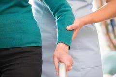 Höga händer för kvinna` s på att gå ramen med omsorgarbetaren i Backgr arkivfoto