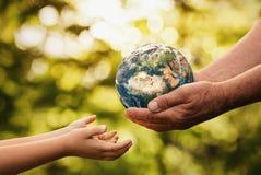 Höga händer som ger planetjord till ett barn royaltyfri foto