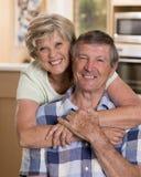 Höga härliga mellersta ålderpar omkring 70 år gammalt le lyckligt tillsammans hemmastatt kök som ser sött i den livstidmaken Arkivfoton