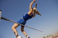 Höga Jumper In Midair Over Bar arkivbild