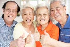 Höga kinesiska vänner som hemma kopplar av på sofaen Royaltyfri Bild