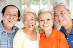 Höga kinesiska vänner som hemma kopplar av på sofaen Royaltyfri Fotografi