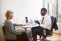 Höga kvinnamöten med den manliga kirurgen In Office för doktor Financial Advisor Cosmetic arkivbild
