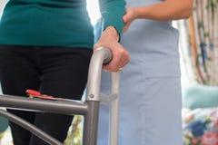 Höga kvinnas händer på att gå ramen med omsorgarbetaren i Backgro royaltyfri bild