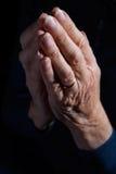 Höga kvinnas händer som knäppas fast i bön arkivfoto