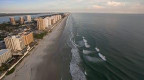 Höga löneförhöjningbyggnader på Florida seglar utmed kusten på solnedgången Arkivfoto