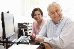 Höga latinamerikanska par som hemma arbetar på datoren Arkivbilder