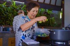 Höga lyckliga och härliga pensionerade asiatiska japanska par som tillsammans lagar mat hemmastatt kök som tycker om förbereda må royaltyfri bild