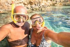 Höga lyckliga par som tar en selfie på den blåa lagun i Malta royaltyfri bild
