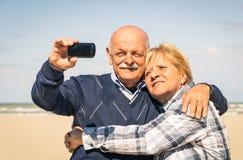 Höga lyckliga par som tar en selfie på stranden Fotografering för Bildbyråer