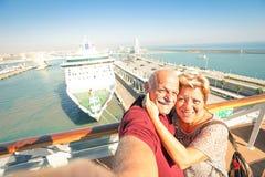 Höga lyckliga par som tar selfie på skeppet på den Barcelona hamnen arkivfoton