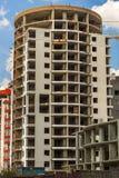 Höga mång--våning byggnader under konstruktions- och kranagains Arkivfoton