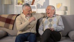 Höga manliga vänner som hemma talar och skrattar på soffan, angenäm konversation stock video