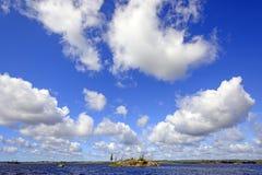 Höga moln över vildmark en sjö Royaltyfri Foto