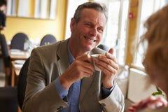 Höga par dricker kaffe på restaurangen, över skuldrasikt Arkivfoton