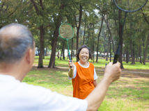 Höga par eller vänner som spelar badminton Arkivfoto